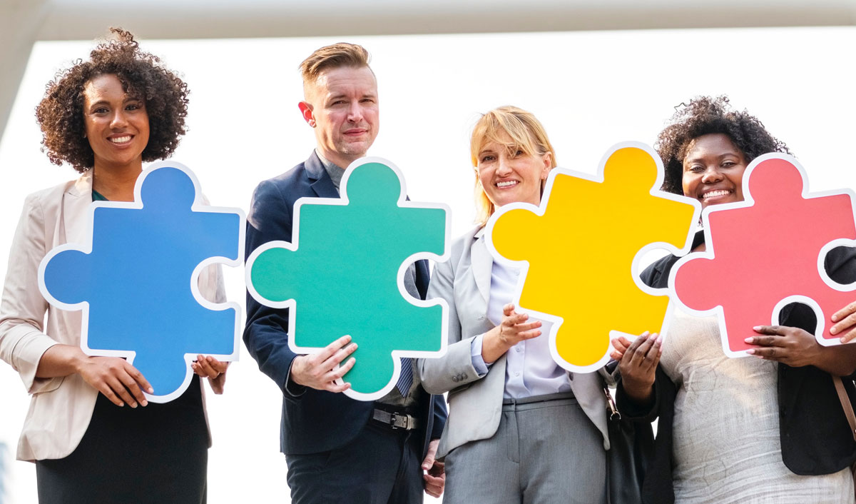 A diverse group of a four business men and business women each holding a large colorful puzzle piece to represent the four different types of personality selling styles.
