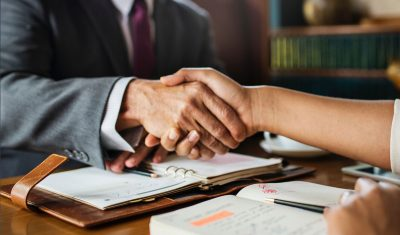 Two business people shaking hands to close a deal.